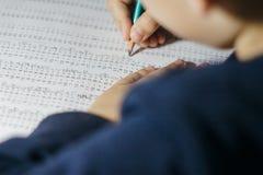 El niño soluciona ejemplos de las matemáticas Imagen de archivo