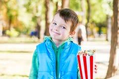 El niño sonriente con un cubo de palomitas a disposición camina en el parque imagenes de archivo