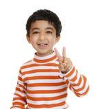 El niño sonriente contellea una muestra de la victoria Imagen de archivo