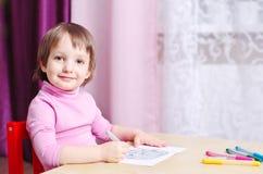 El niño sonriente dibuja una imagen de los marcadores coloridos fotografía de archivo libre de regalías