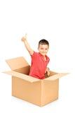 El niño sonriente en una caja de papel que daba el pulgar para arriba y que lo miraba vino Imágenes de archivo libres de regalías