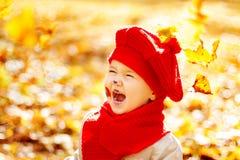 El niño sonriente feliz en parque del otoño, se cae las hojas amarillas imagen de archivo