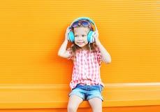 El niño sonriente feliz escucha la música en auriculares sobre naranja colorida Fotografía de archivo