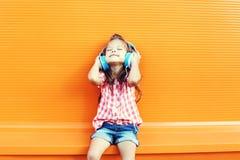 El niño sonriente feliz goza escucha la música en auriculares sobre naranja Foto de archivo libre de regalías