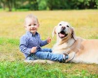 El niño sonriente feliz y el golden retriever del niño pequeño persiguen sentarse en hierba Foto de archivo