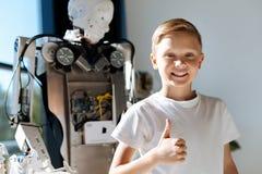 El niño sonriente que muestra los pulgares sube cerca del robot humano Foto de archivo