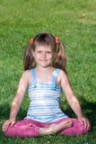 El niño sonriente se sienta en asana en hierba verde Fotografía de archivo libre de regalías