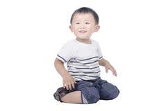 El niño sonriente se sienta en el piso Imágenes de archivo libres de regalías