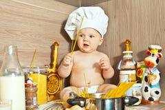 El niño sorprendido el cocinero del cocinero cocina la comida Fotografía de archivo