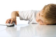El niño sostiene el ratón del ordenador Imagenes de archivo