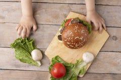 El niño sostiene la hamburguesa de la seta sobre la tajadera en la tabla de madera imagen de archivo