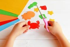 El niño sostiene las tijeras y corta el cangrejo de papel Lección del arte en guardería Animales de mar de papel, pulpo, pescado, Fotos de archivo