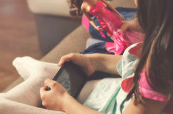 El niño sostiene smartphone mientras que se sienta en el sofá en casa Imagenes de archivo