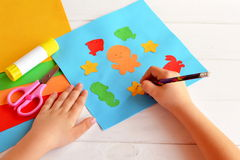 El niño sostiene un lápiz y dibuja Hojas del papel coloreado, tijeras, pegamento, sistema para el arte de los niños Foto de archivo libre de regalías