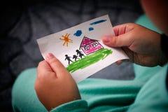 El niño sostiene una casa exhausta con la familia Foto de archivo