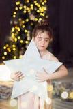 El niño sostiene una estrella en el fondo de un árbol de navidad muchacha que sueña con los ojos cerrados imagenes de archivo