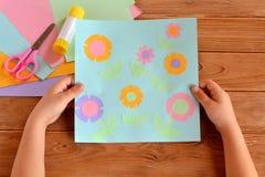 El niño sostiene una tarjeta con las flores en sus manos Pegamento, tijeras, hojas de papel en una tabla de madera Foto de archivo