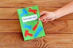 El niño sostiene una tarjeta disponible Father& x27 de la tarjeta de felicitación; día de s Father& feliz x27; día de s Idea del  foto de archivo