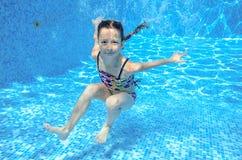 El niño subacuático activo feliz nada en la piscina, natación sana hermosa de la muchacha Foto de archivo libre de regalías