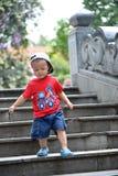 El niño sube abajo las escaleras Fotografía de archivo