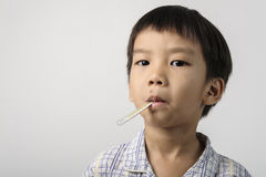 El niño tiene un herpes en boca y la medición de la fiebre imagen de archivo