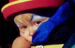El niño tiene un maskerade del payaso Imagenes de archivo