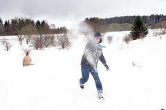 El niño tiene una lucha de la bola de nieve en blanco Imagen de archivo