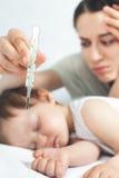 El niño tiene una temperatura alta o una fiebre, usando un termómetro fotografía de archivo libre de regalías