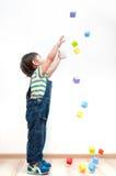 El niño tira de las manos hacia arriba para los juguetes fotos de archivo
