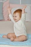 El niño tira las manos hacia arriba y sonríe Foto de archivo libre de regalías