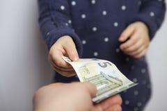 El niño toma el dinero imágenes de archivo libres de regalías