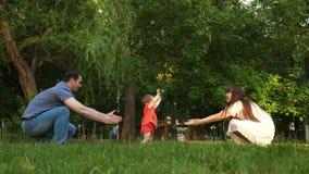 El niño toma las primeras medidas en césped en el parque en verano, mamá y el papá aprende caminar el bebé almacen de video