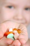 El niño toma las vitaminas Imágenes de archivo libres de regalías
