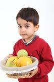 El niño trae la fruta de la cesta Fotos de archivo