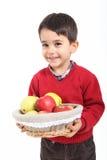 El niño trae la fruta de la cesta Fotografía de archivo