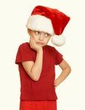 El niño triste de la muchacha en el retrato en blanco aislado, concepto del sombrero de santa del día de fiesta de la Navidad, am Fotografía de archivo