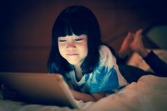 El niño usando la tableta en línea comunica la red social Imagen de archivo