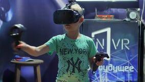 El niño utiliza la exhibición de las VR-auriculares para el juego de la realidad virtual, tecnologías modernas en la acción, indi almacen de metraje de vídeo