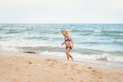 El niño va a lo largo de la costa Fotos de archivo