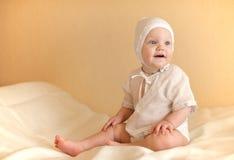 El niño vestido en blanco se sienta en el smilin de la cama Fotos de archivo