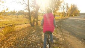 El ni?o viaja en bici en el camino los deportes caminan a la muchacha adolescente en una bici Una chica joven en una chaqueta roj metrajes