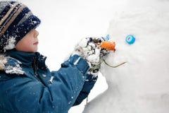 El niño y el muñeco de nieve Fotografía de archivo libre de regalías