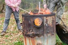 El niño y el padre están sosteniendo las salchichas en los palillos en un fuego abierto de un pote del fuego Imagenes de archivo