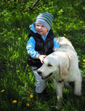El niño y el perro en el jardín Foto de archivo libre de regalías