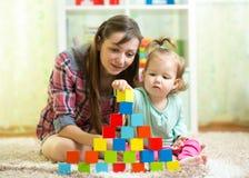 El niño y la madre del niño construyen la torre que juega los juguetes de madera en casa o el cuarto de niños foto de archivo