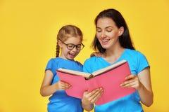 El niño y la madre están leyendo el libro Fotos de archivo libres de regalías