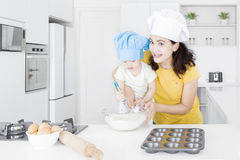 El niño y la madre hacen la torta imagenes de archivo