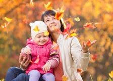 El niño y la madre hermosa juegan y lanzan las hojas al aire libre en otoño Foto de archivo libre de regalías