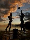 El niño y la madre juegan con la bola en puesta del sol Fotografía de archivo libre de regalías