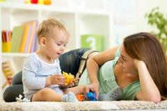 El niño y su mamá juegan el parque zoológico que sostiene los juguetes animales Foto de archivo